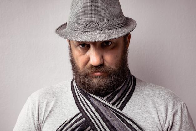 Close de um homem barbudo vestindo uma camiseta cinza claro, chapéu e lenço em um fundo cinza
