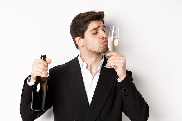 Close de um homem bonito de terno, beijando taça com champanhe, embebedando-se em uma festa, em pé contra um fundo branco
