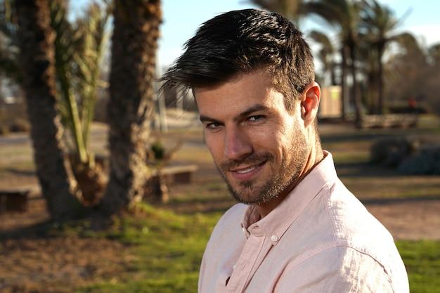 Close de um homem bonito e atraente com um sorriso unilateral