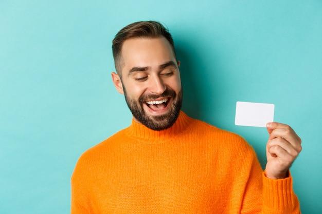 Close de um homem bonito e caucasiano, mostrando o cartão de crédito e sorrindo
