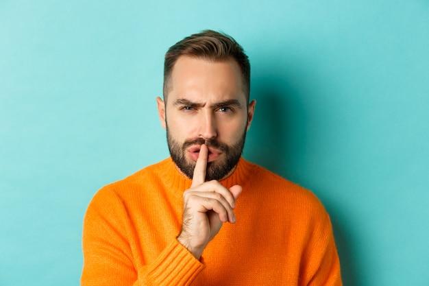 Close de um homem carrancudo irritado, silenciando a câmera, pressionando o dedo nos lábios, mostrando um gesto tabu