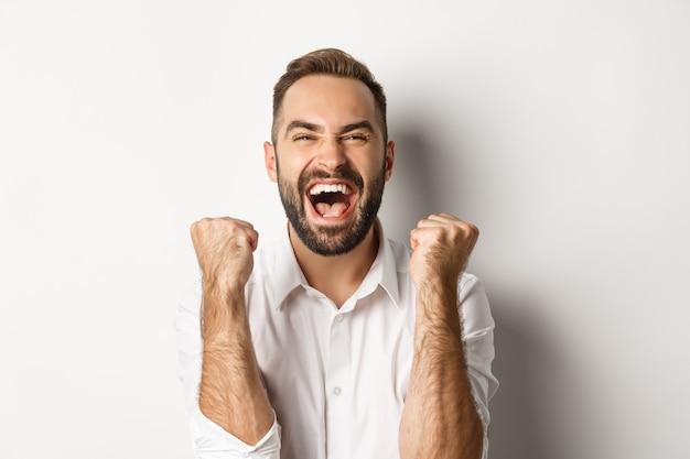 Close de um homem caucasiano de sucesso regozijando-se com a vitória, dando socos e comemorando a vitória, atingindo a meta e gritando de alegria