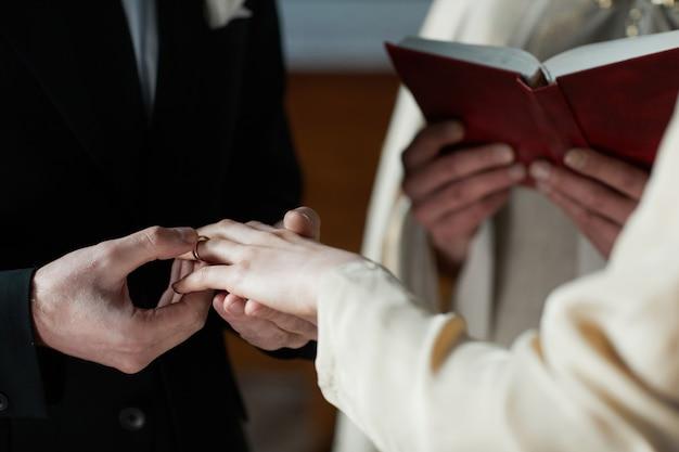 Close de um homem colocando o anel na mão de sua esposa durante a cerimônia na igreja