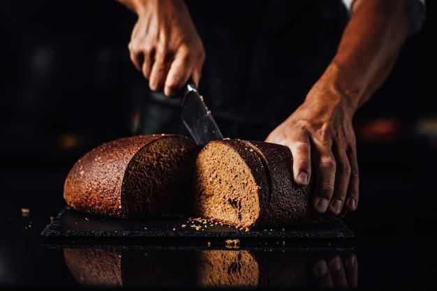 Close de um homem cortando pão integral em um fundo de tábua de pedra