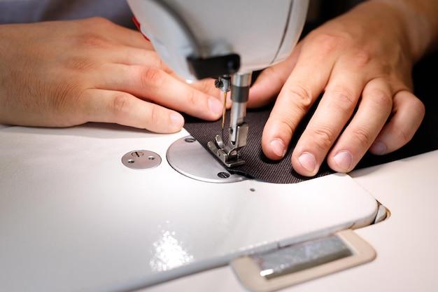 Close de um homem costurando em uma máquina de costura