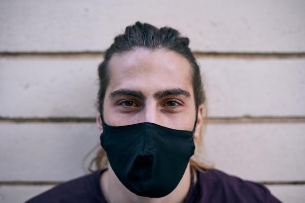 Close de um homem de cabelos compridos na rua, olhando para a câmera, enquanto usava uma máscara contra a pandemia do coronavírus
