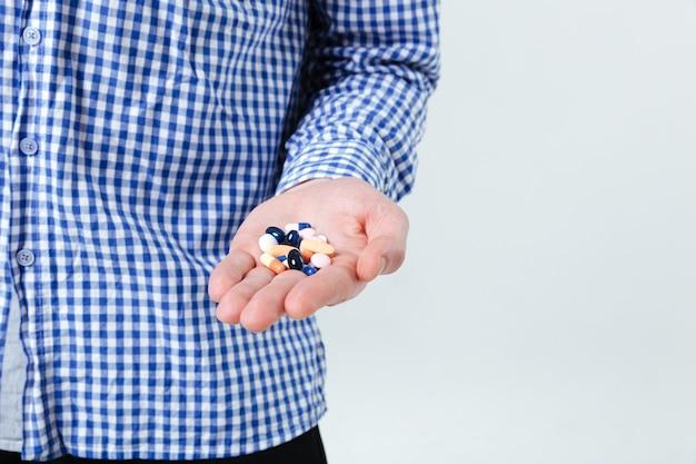 Close de um homem de camisa quadriculada em pé e segurando comprimidos na parede branca