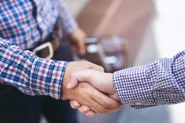 Close de um homem de negócios com bagagem viajar aperto de mão entre dois colegas cumprimentar