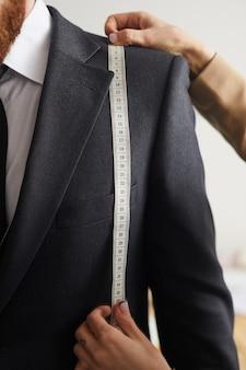 Close de um homem de terno em pé na oficina enquanto o designer mede o comprimento dos seios