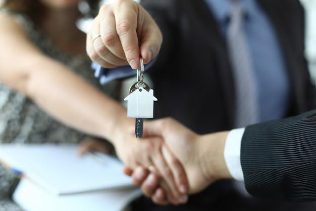 Close de um homem e uma mulher apertando as mãos das chaves do apartamento nas mãos do agente de seguros