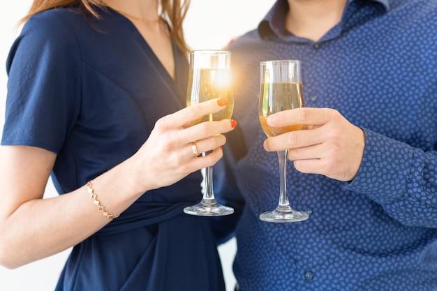 Close de um homem e uma mulher comemorando a festa de natal ou ano novo com luzes de bengala e taças de champanhe