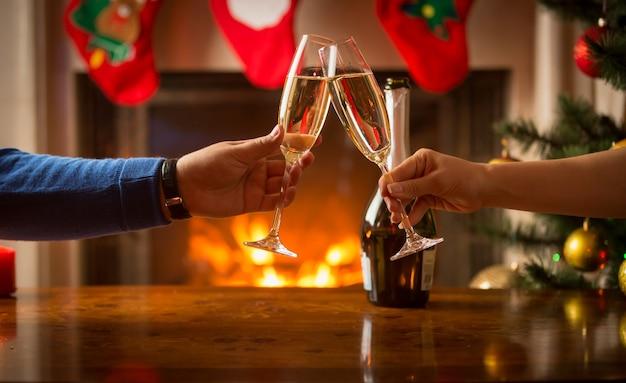 Close de um homem e uma mulher comemorando o natal e tilintando de taças com champanhe na lareira