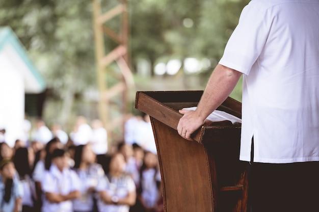 Close de um homem em pé perto de um suporte de madeira lendo a bíblia para crianças