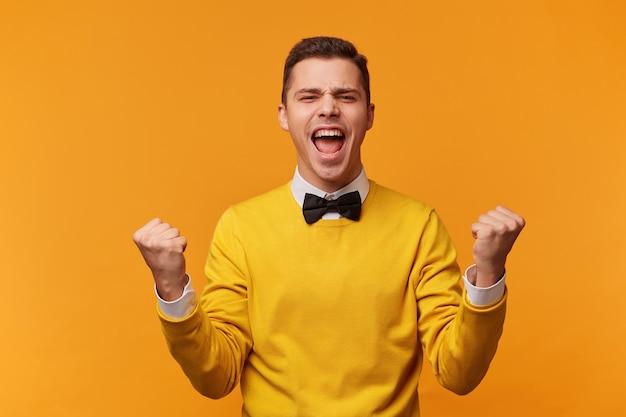 Close de um homem emocional isolado na parede amarela, mostrando dentes brancos enquanto grita