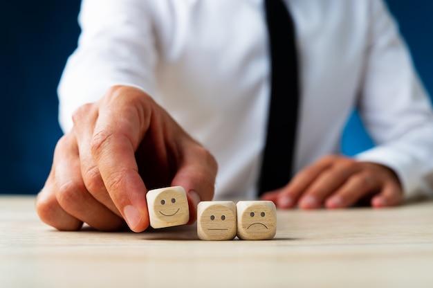 Close de um homem escolhendo dados de madeira com uma cara sorridente entre três opções