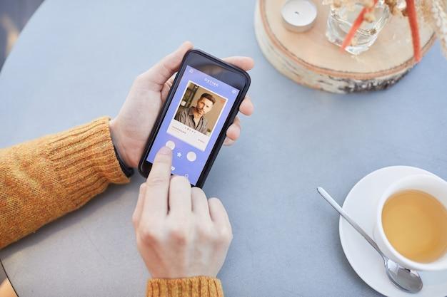Close de um homem escolhendo um companheiro para uma conversa online usando o aplicativo em seu telefone celular
