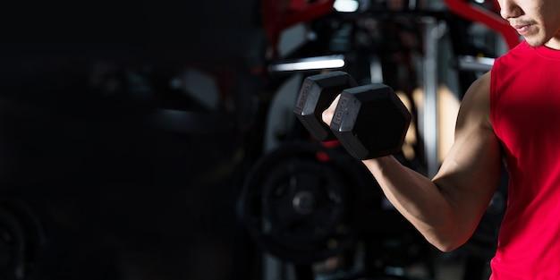 Close de um homem fitness, um cara bonito e atlético fazendo exercícios com halteres