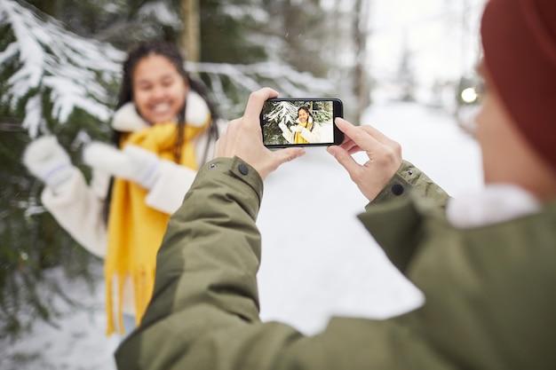 Close de um homem fotografando uma mulher no celular enquanto ela posa contra as árvores nevadas ao ar livre