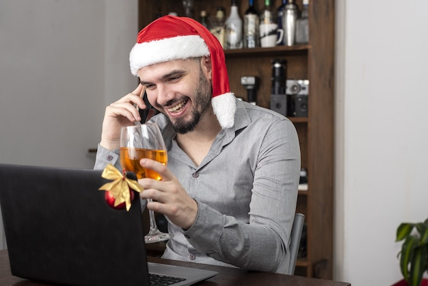 Close de um homem hispânico com um chapéu de papai noel, apreciando seu vinho e falando ao telefone