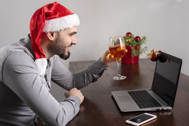 Close de um homem hispânico usando um chapéu de papai noel, apreciando seu vinho e tendo uma reunião on-line
