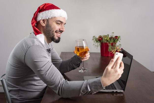Close de um homem hispânico usando um chapéu de papai noel, apreciando seu vinho e tirando uma selfie
