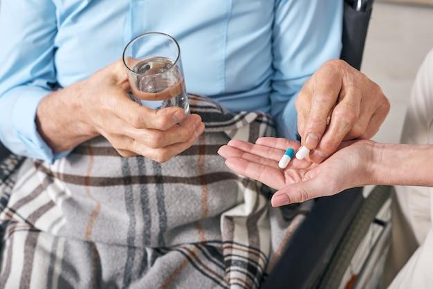 Close de um homem idoso irreconhecível sentado sob um cobertor em uma cadeira de rodas e tomando comprimidos dados pela enfermeira