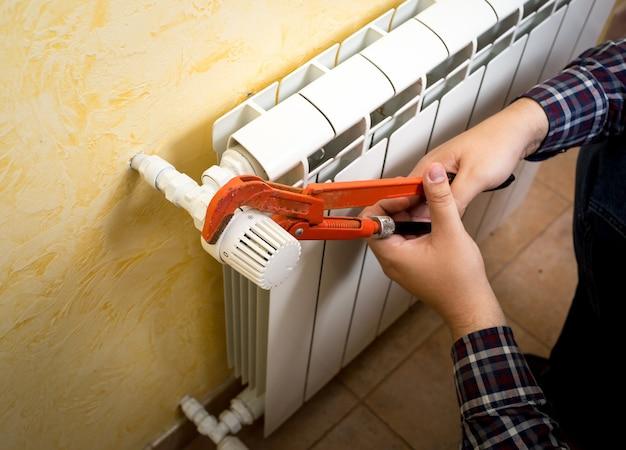 Close de um homem instalando a válvula do radiador com um alicate de encanador vermelho