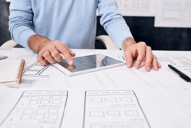 Close de um homem irreconhecível sentado à mesa com esboços e usando um tablet durante o desenvolvimento do design do aplicativo