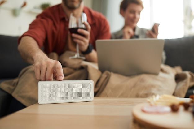 Close de um homem ligando o rádio na mesa enquanto bebe vinho com uma mulher no sofá
