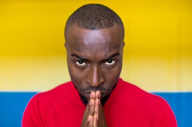 Close de um homem negro africano concentrado e focado com as mãos unidas