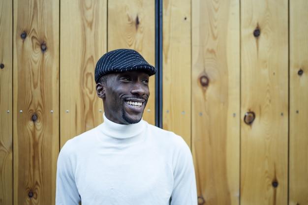 Close de um homem negro de chapéu e gola olímpica