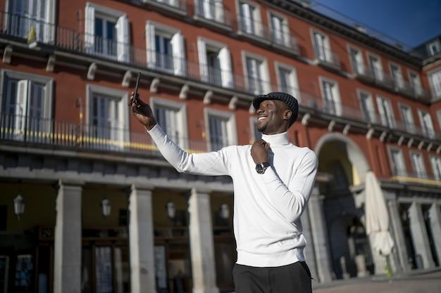 Close de um homem negro de gola alta e chapéu tirando uma selfie