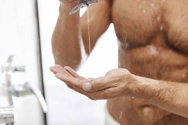Close de um homem nu colocando gel de banho