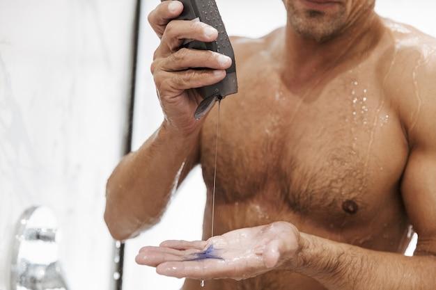 Close de um homem nu sexy colocando gel de banho