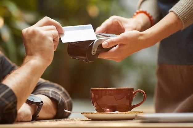 Close de um homem pagando com cartão de crédito o pedido dele para o garçom no café