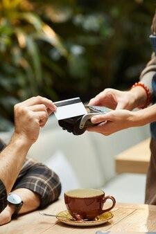 Close de um homem pagando pela xícara de café com cartão de crédito para o garçom no restaurante