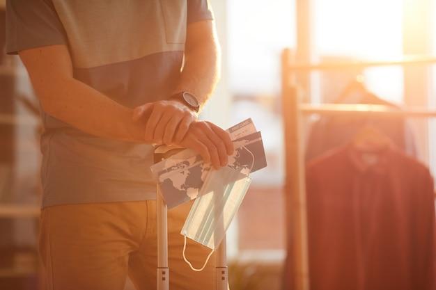 Close de um homem parado com bagagem e passagens, esperando seu voo, em viagem de negócios