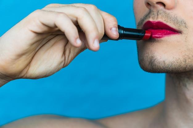 Close de um homem pintando os lábios de vermelho em uma parede azul
