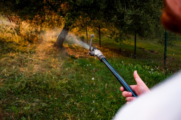 Close de um homem regando seu jardim com uma mangueira jorrando água