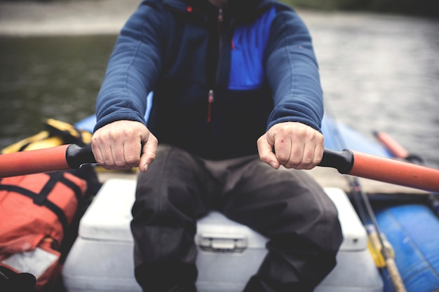 Close de um homem remando em um barco no rio do estado de washington