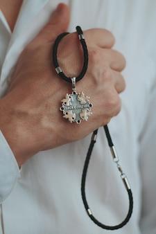 Close de um homem segurando um colar com um pingente de prata e um cordão preto