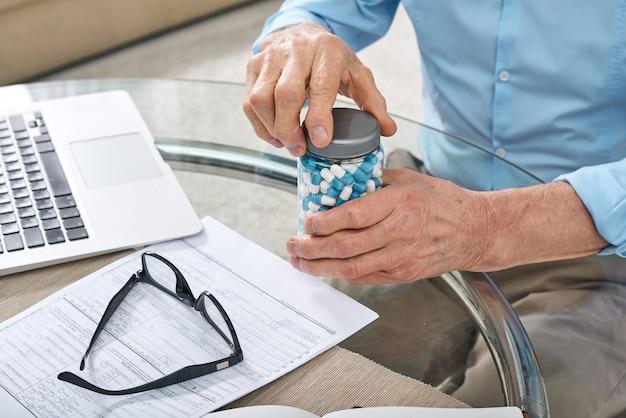 Close de um homem sênior irreconhecível sentado à mesa com o laptop e abrindo o frasco de comprimidos enquanto se prepara para tomar a medicação