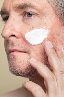 Close de um homem sênior usando um creme hidratante para a rotina de cuidados com a pele