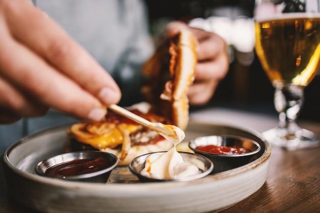 Close de um homem sentado em um restaurante colocando maionese em um hambúrguer