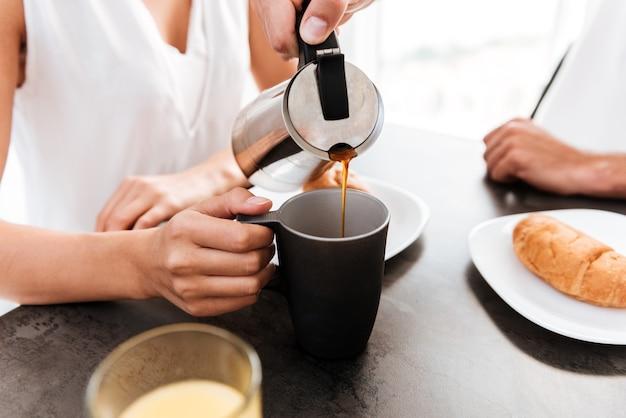 Close de um homem servindo café na xícara da namorada na cozinha