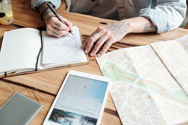 Close de um homem tatuado sentado à mesa e fazendo uma lista de tarefas antes da viagem