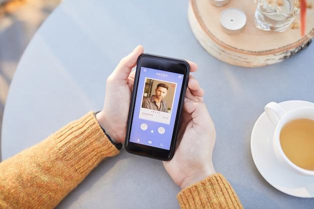 Close de um homem usando seu telefone celular para namorar on-line, enquanto está sentado à mesa