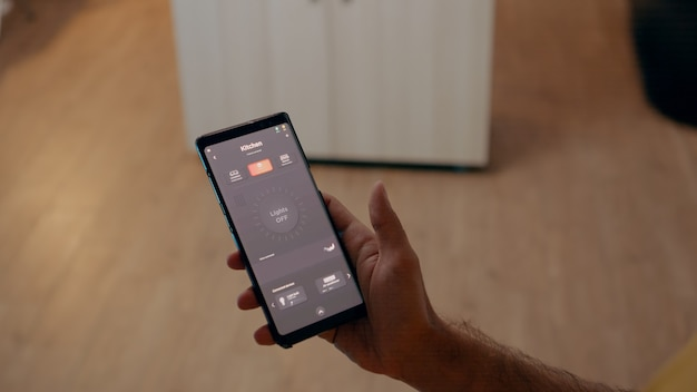 Close de um homem usando um aplicativo ativado por voz para acender as lâmpadas em uma casa inteligente com sistema de automação