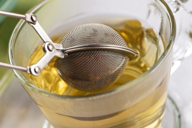 Close de um infusor com chá em uma xícara com água quente.