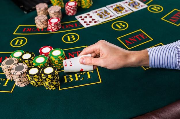 Close de um jogador de pôquer levantando as pontas de duas cartas de ases na mesa verde do cassino com ases